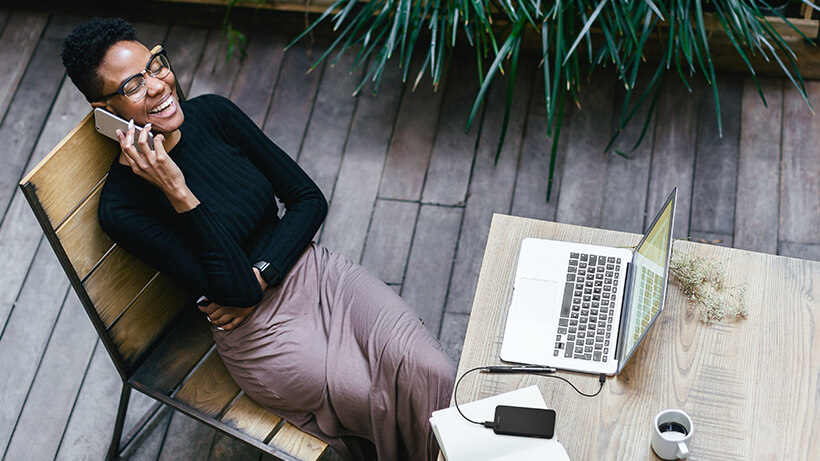 Woman on the phone while BOOST↑CHARGE™ Power Bank is charging her MacBook