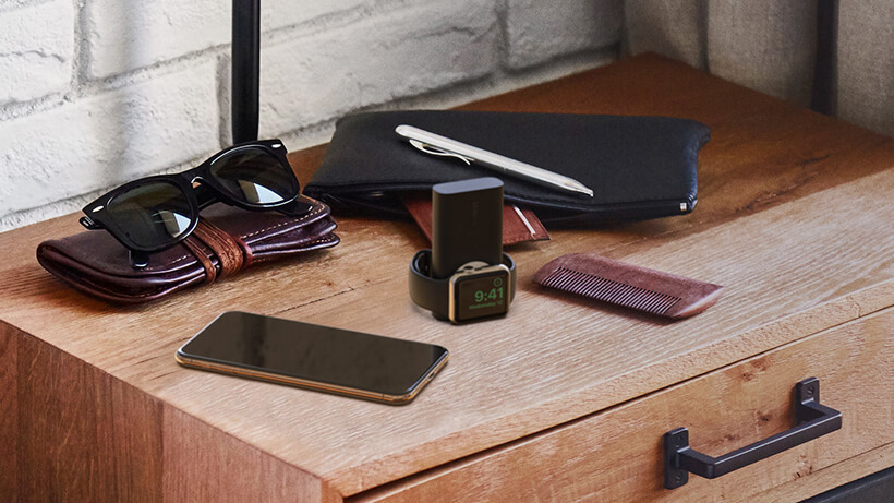 BOOST↑CHARGE™ Power Bank on a nightstand, next to a pocket bag
