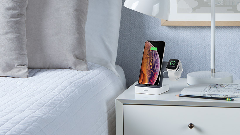 iPhone and Apple Watch charging on the dock, on a nightstand