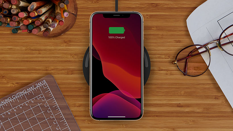 BOOST↑CHARGE Wireless Charging Pad charging a smartphone on a desk