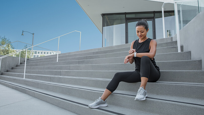 Jogger sitting on stairs, checking their Apple Watch
