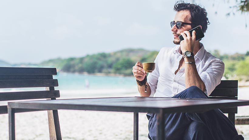Man sitting at a table at a beach on his iPhone XR